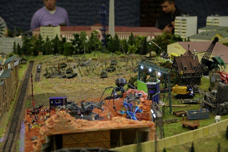Гранд макет: киносъемочная площадка. Снимают вторжение марсиан. Справа подъёмным краном собирают замок с горгульями для следующих съемок