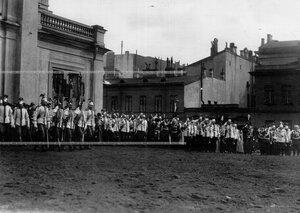 Император Николай II и свита присутствуют при выносе штандартов из манежа полка.