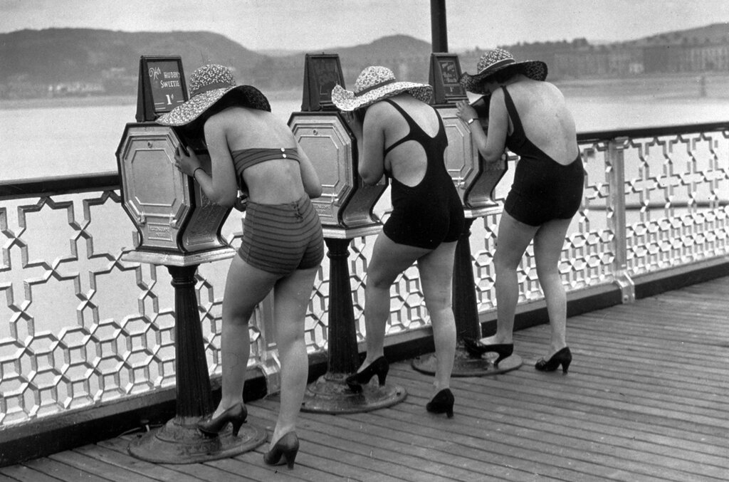 27th June 1935:  Holidaymakers view 'What The Butler Saw' picture peep shows (mutoscopes) on the pier at Llandudno, North Wales.