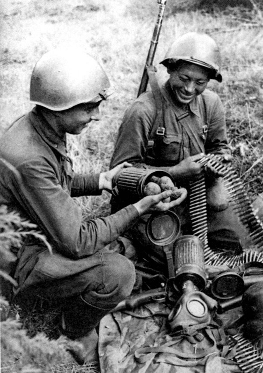 1941. Русские солдаты осматривают трофеи, взятые у немцев и обнаруживают в футляре для противогаза картофель