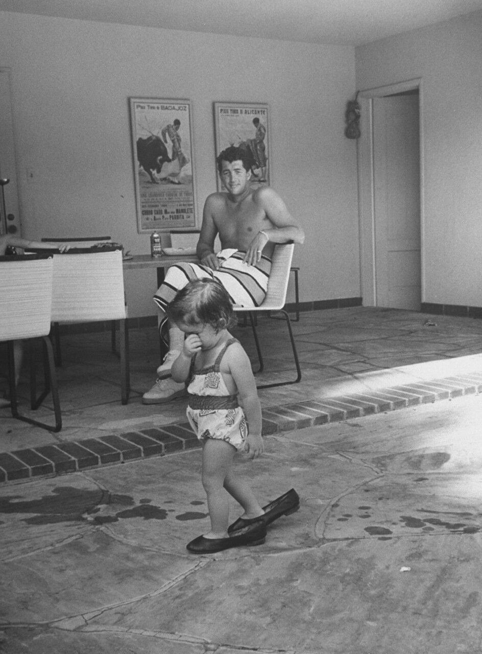 1958. Дин Мартин наблюдает за своей дочерью Джиной Каролиной, шагающей в его обуви по дому в  Беверли Хиллз