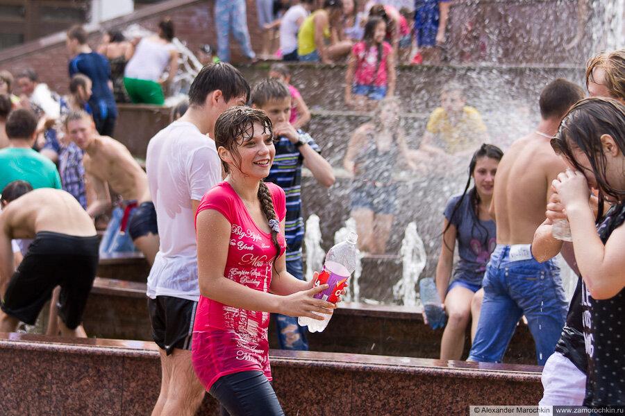 Участница водного батла в мокрой одежде поливает водой из бутылки