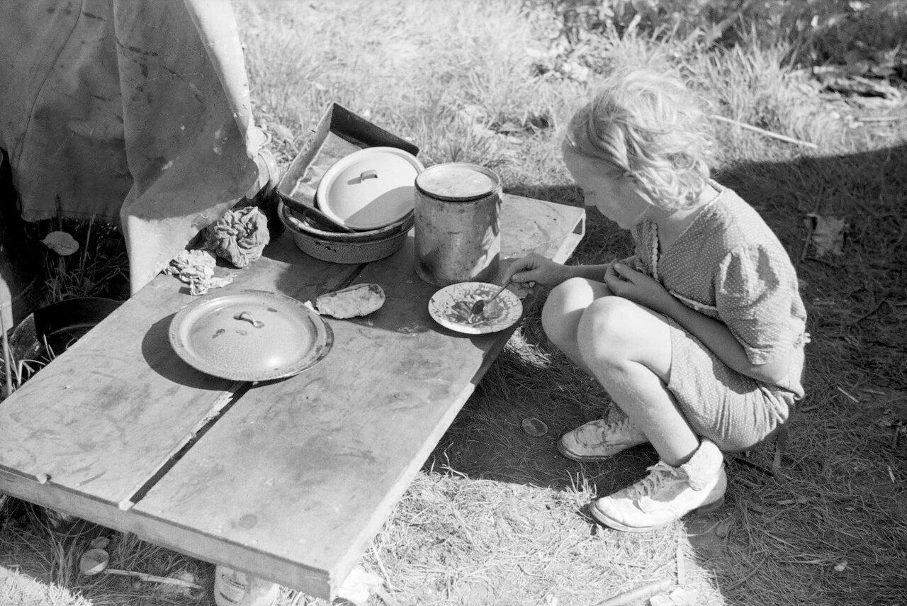 Ребенок сезонных рабочих ест возле палатки, Округ Берриен, штат Мичиган, 1940