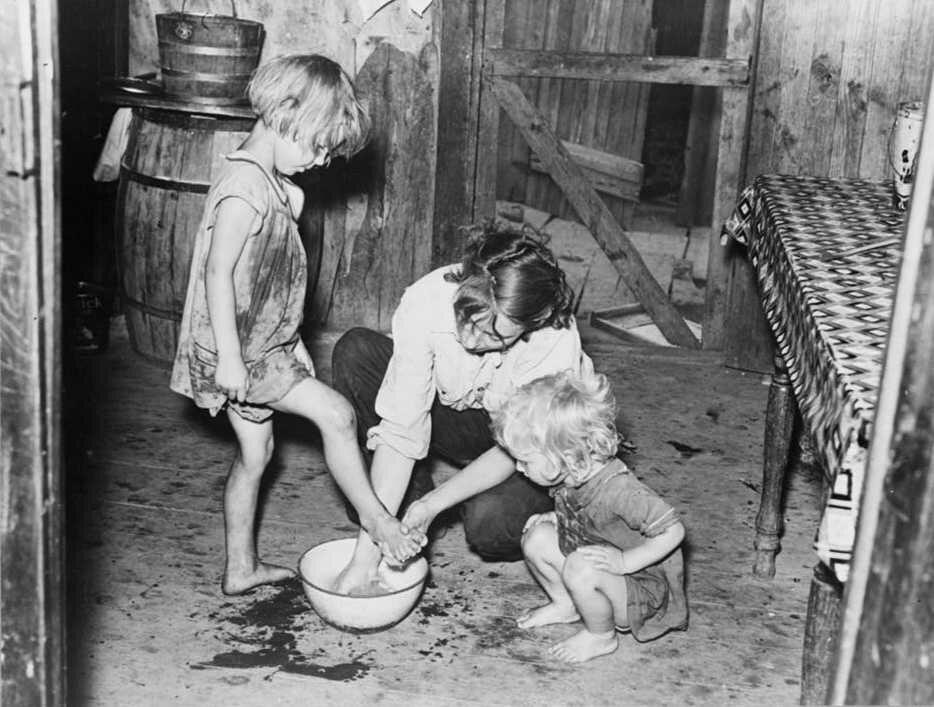 Мать моет ноги детям в лачуге испольщика в Миссури, 1938