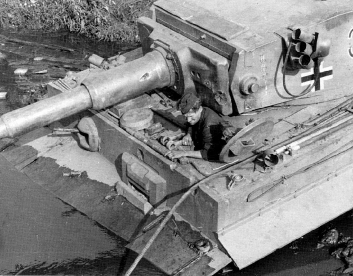 1943. Украина, Знаменка, водитель Panzerkampfwagen VI Tiger из люка машины рассматривает застрявший в грязи на берегу реки танк