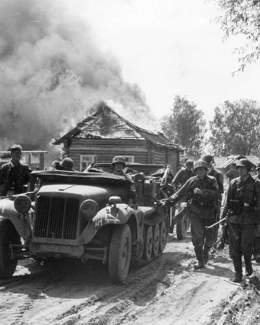 1941. Тягач Sonderkraftfahrzeug 10  и солдаты дивизии СС Рейх проезжают через деревню