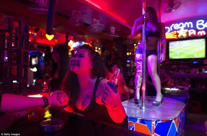 Женщина, работающая в баре, разговаривает с посетителем.