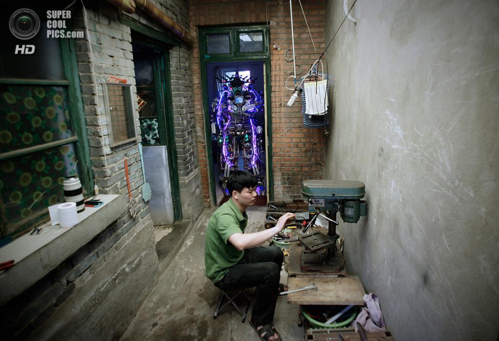 Китай. Пекин. 15 мая. Изобретатель Тао Сянли работает над усовершенствованием своего самодельног