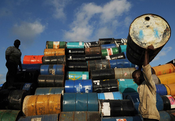 1. Местный житель разбирает нефтяной баррель на окраине Порт-о-Пренс, 13 февраля 2015. В хозяйс