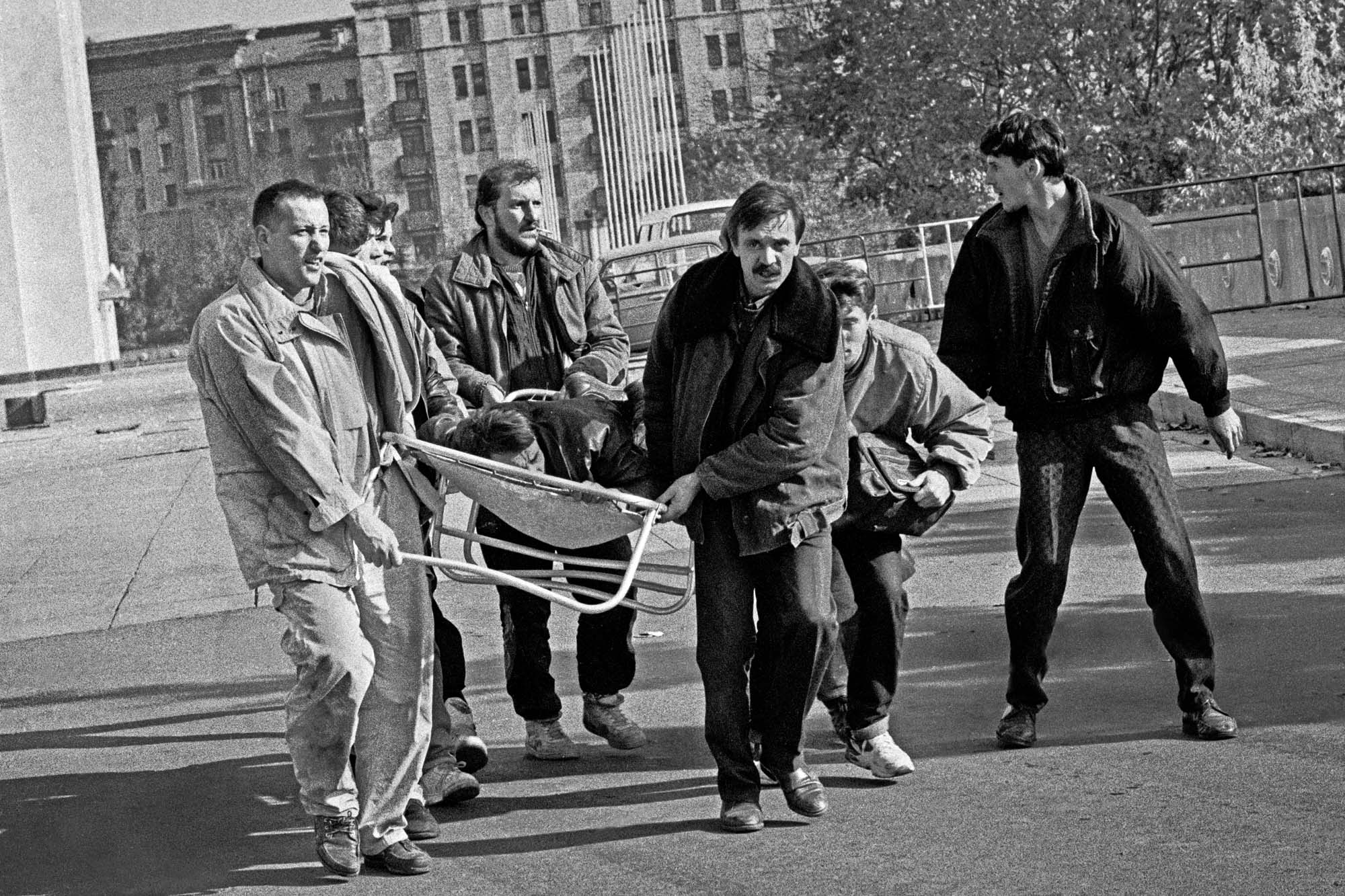 3 октября раненого человека уносят на носилках возле Дома Советов