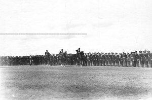 Император Николай II и сопровождающие его офицеры объезжают юнкеров артиллерийских училищ, выстроившихся на военном поле.