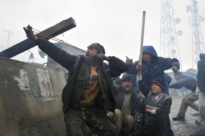 An Afghan man aims a sling shot toward U