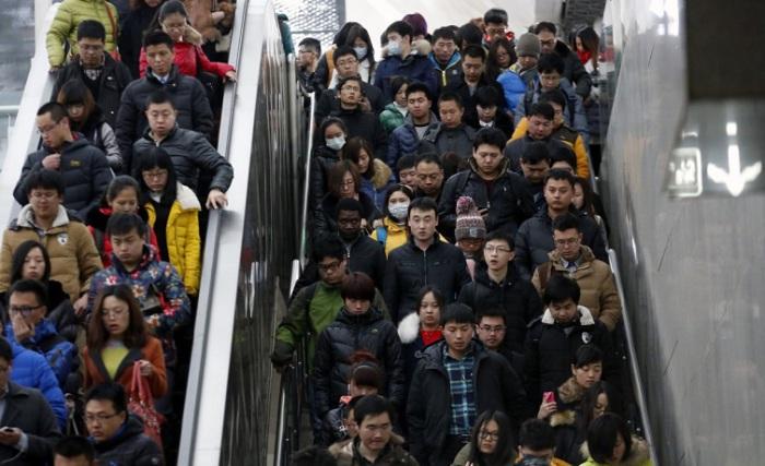 Люди спускаются на эскалаторе и сходят по лестнице, направляясь к платформе метро в час пик в Пекине
