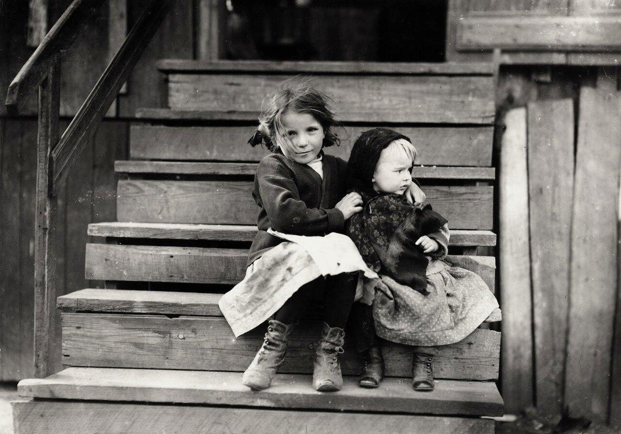 Маленькая Джулия с ребенком на крыльце дома. Все более взрослые на заводе. 1911