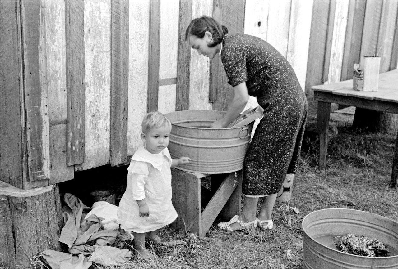 Жена фермера, стирающая одежду и одновременно приглядывающая за сыном. Возле Морганза, Луизиана, 1938
