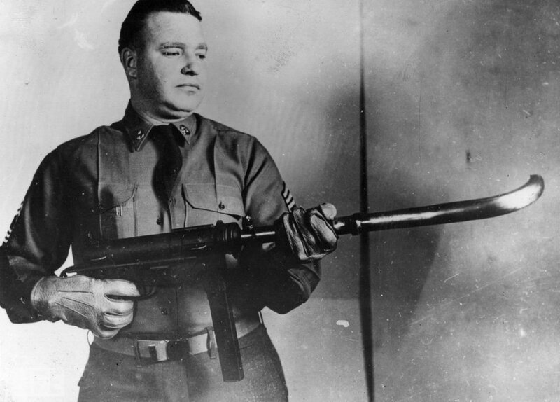 An American soldier demonstrates an M3 Grease Gun that can shoot around corners ca. 1953.jpg