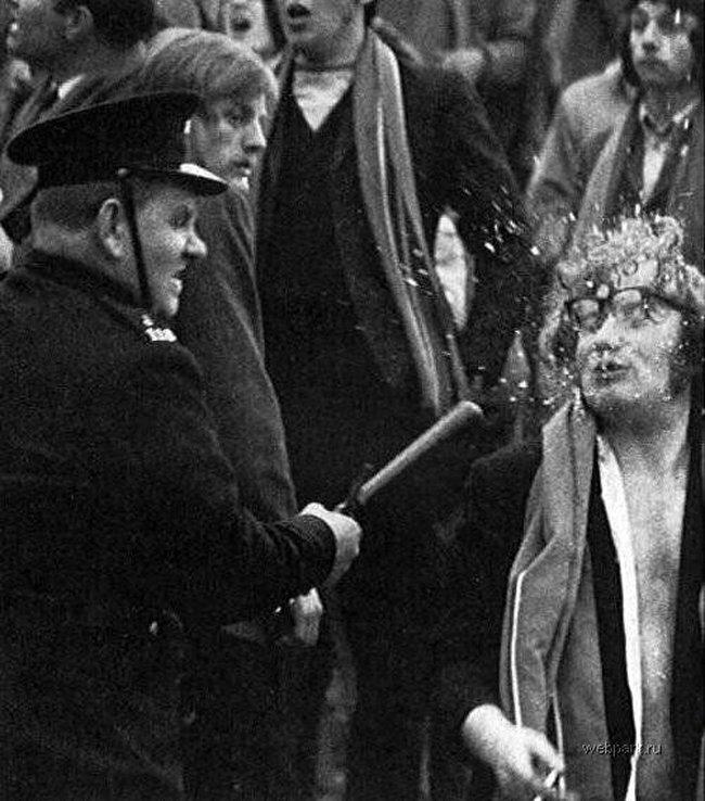 Полицейский разбивает очки демонстранту