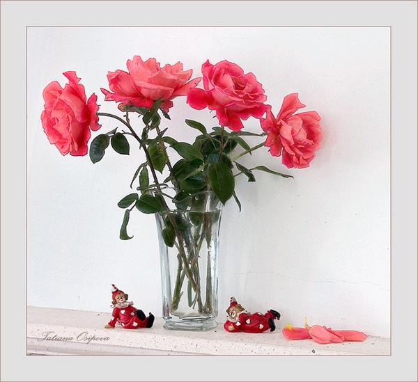 Розы в прозрачной вазе под которой лежат игрушки