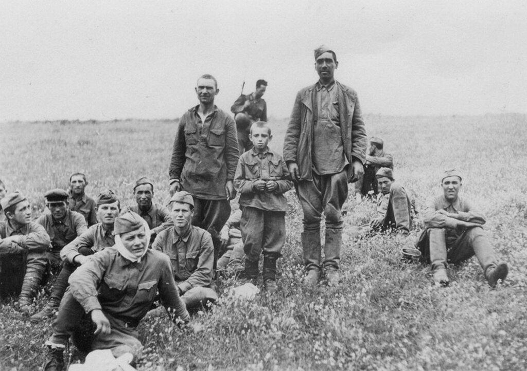 Группа пленных красноармейцев с воспитанником. На заднем плане немецкий конвоир. 1942 г.