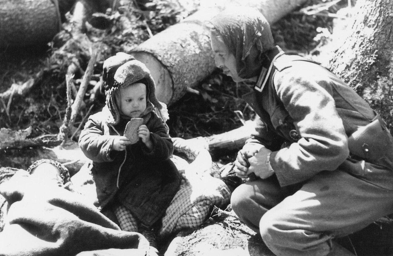 1942.Ленинградская область, Волховский фронь, немец дает кусок хлеба ребенку
