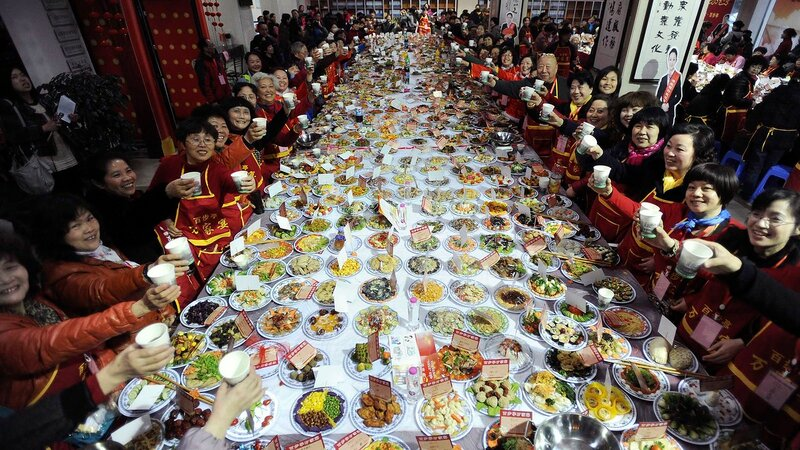 "Residents raise their glasses as they pose for photographs during a ""Ten thousand families dinner"" organized by a local community to celebrate the upcoming Chinese lunar new year in Wuhan"