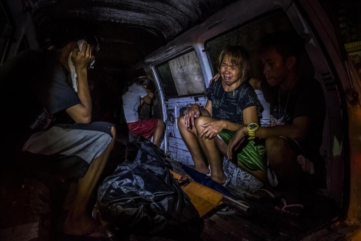 Нелли Диаз плачет над телом своего мужа Крисостомо, который был наркоманом. Его застрелили через нес