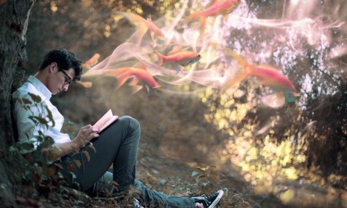 young-man-leaning-against-a-tree-reading-book-with-gold-fishes-flying-out-of-his-head-situation-art-694x417.jpg