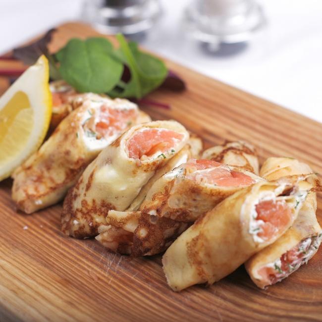 Смажьте блинчики мягким сливочным сыром, сверху поместите ломтик слабосоленой красной рыбы. Посыпьте