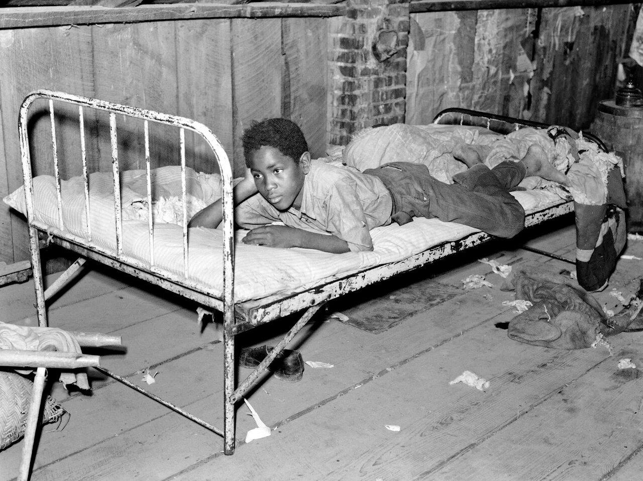 Мальчик отдыхает на кровати в бараке испольщика. Округ Новый Мадрид, Миссури, 1938