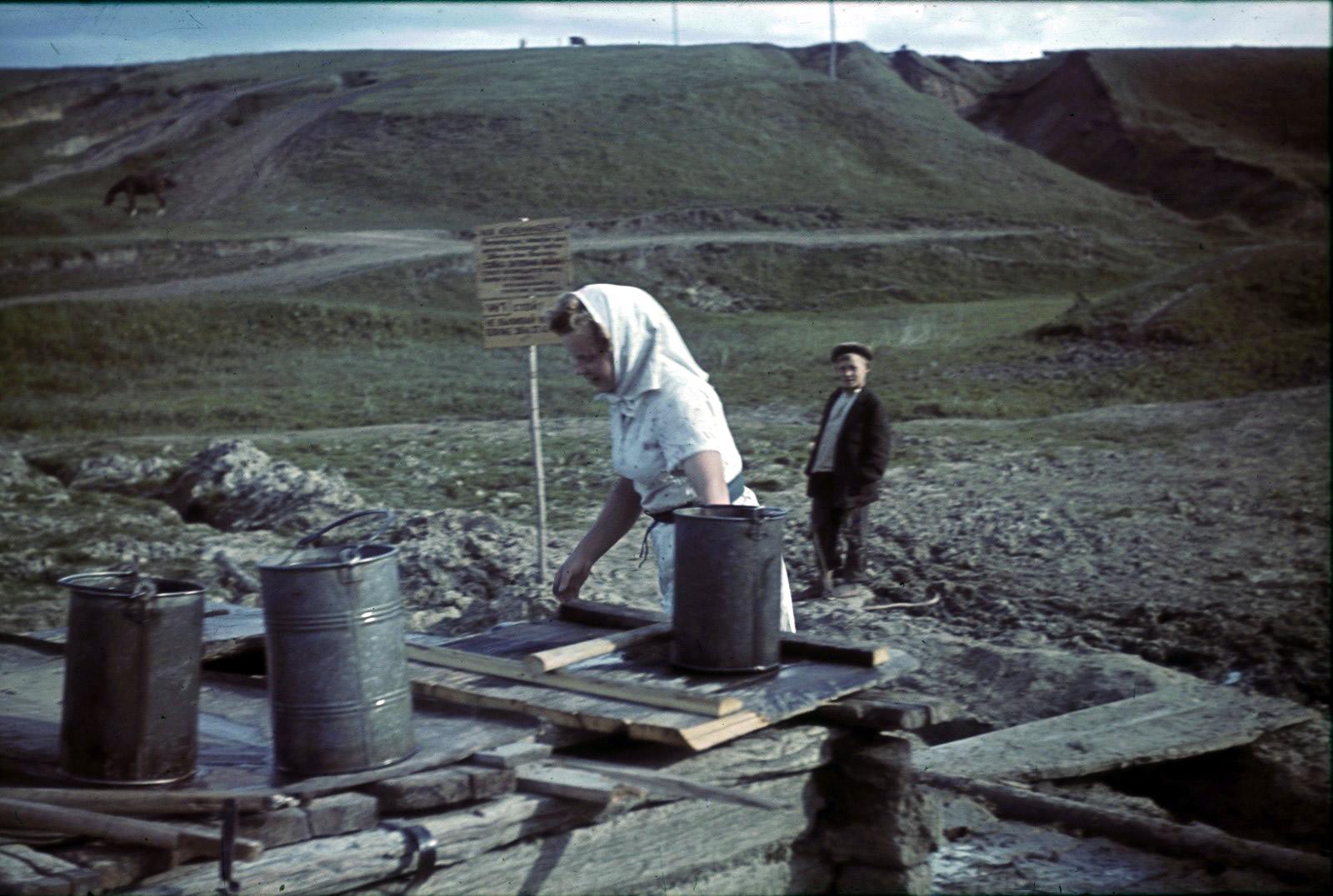 Женщина набирает воду