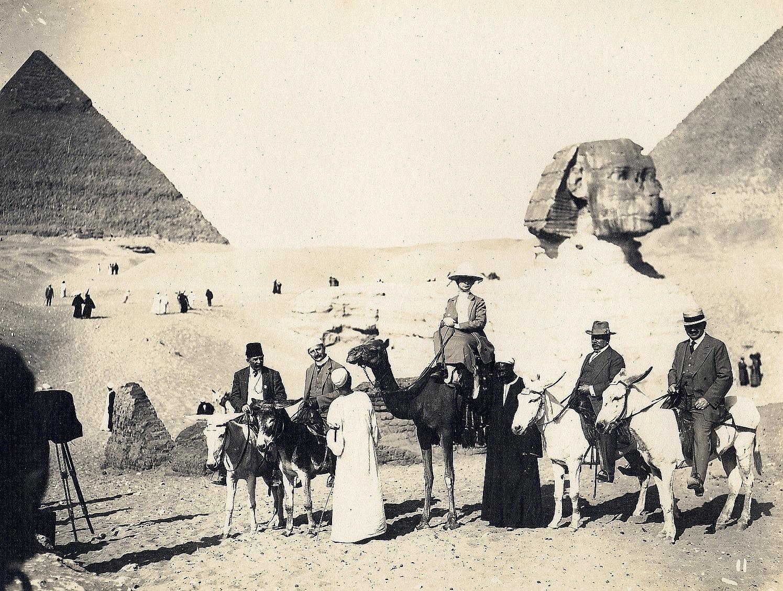 Гиза. Туристы и местные жители на верблюдах и мулах перед Сфинксом