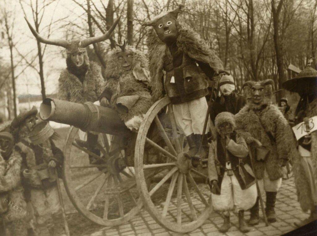 Maskers. Maskerfeesten. Groep gemaskerde en in bontjassen geklede personen op en voor een kanon tijdens het Mohacs Maskerfeest. Plaats onbekend, Hongarije, 1935