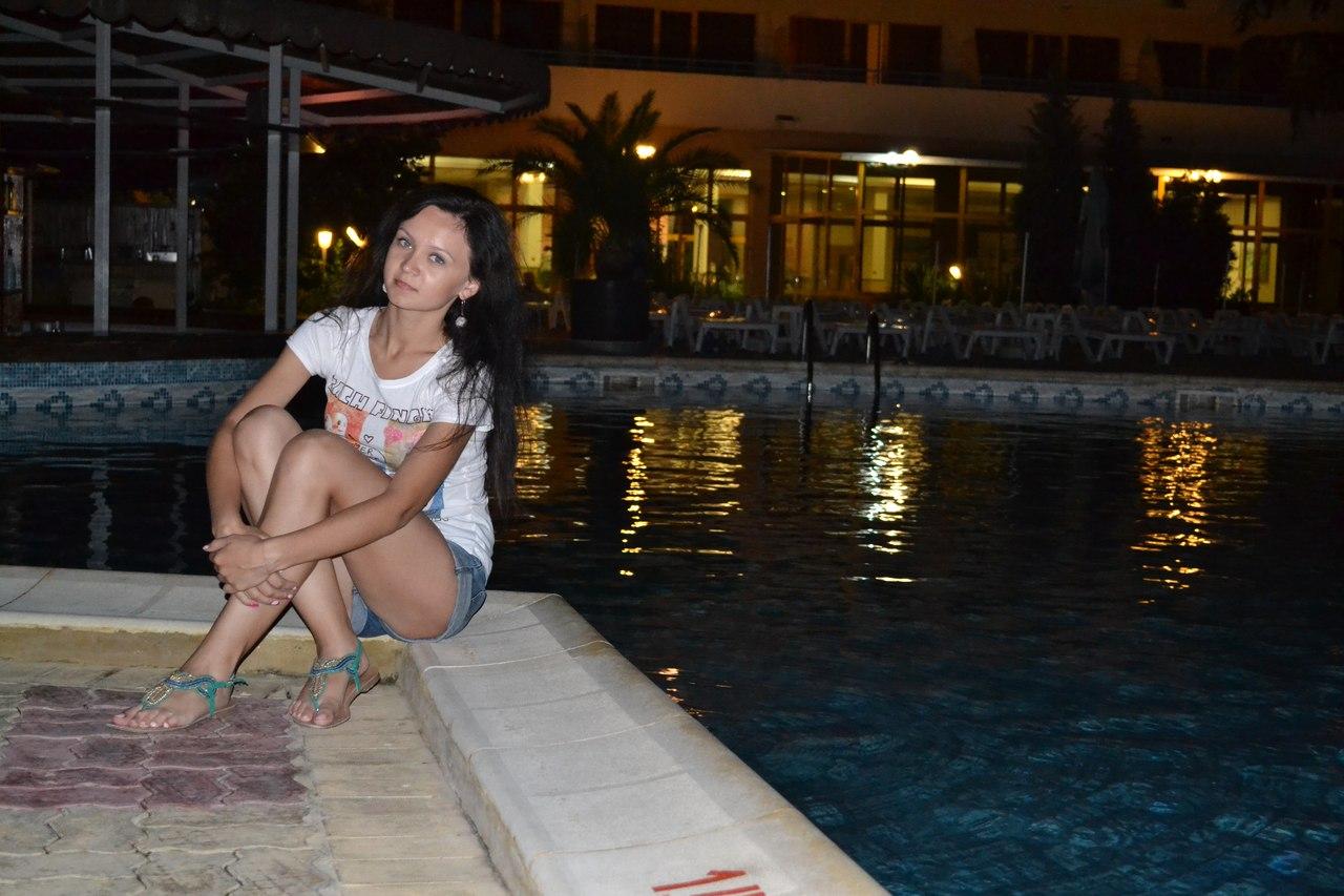 Темноволосая девчонка в шортах возле бассейна