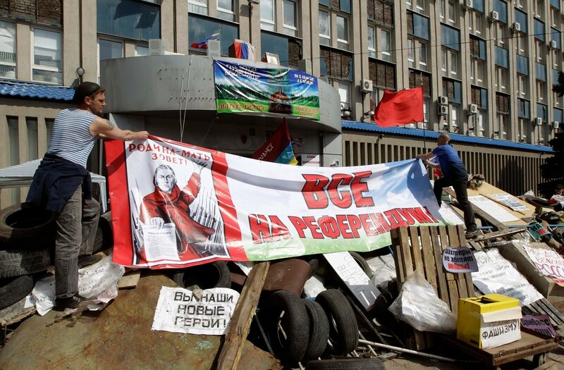 Pro-Russian protesters tie a banner on barricades placed in front of the seized office of the SBU state security service in Luhansk
