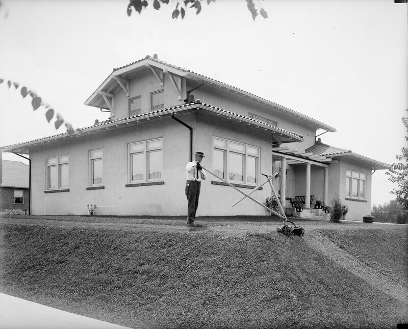 Harry F. Rhoads uses a lawn mower on grass at his Denver, Colorado house, between 1920 and 1930