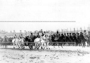 Император Николай II на коне и императрица Александра Федоровна с сыном цесаревичем Алексеем в коляске объезжают полк, выстроенный на параде на плацу у Екатерининского дворца.