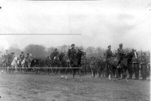 Император Николай II верхом на коне и императрица Александра Федоровна с наследником в коляске объезжают запасные батальоны гвардейской пехоты перед парадом.