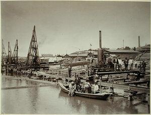 Рабочие на строительстве набережной;на первом плане (в лодке)-водолаз в скафандре