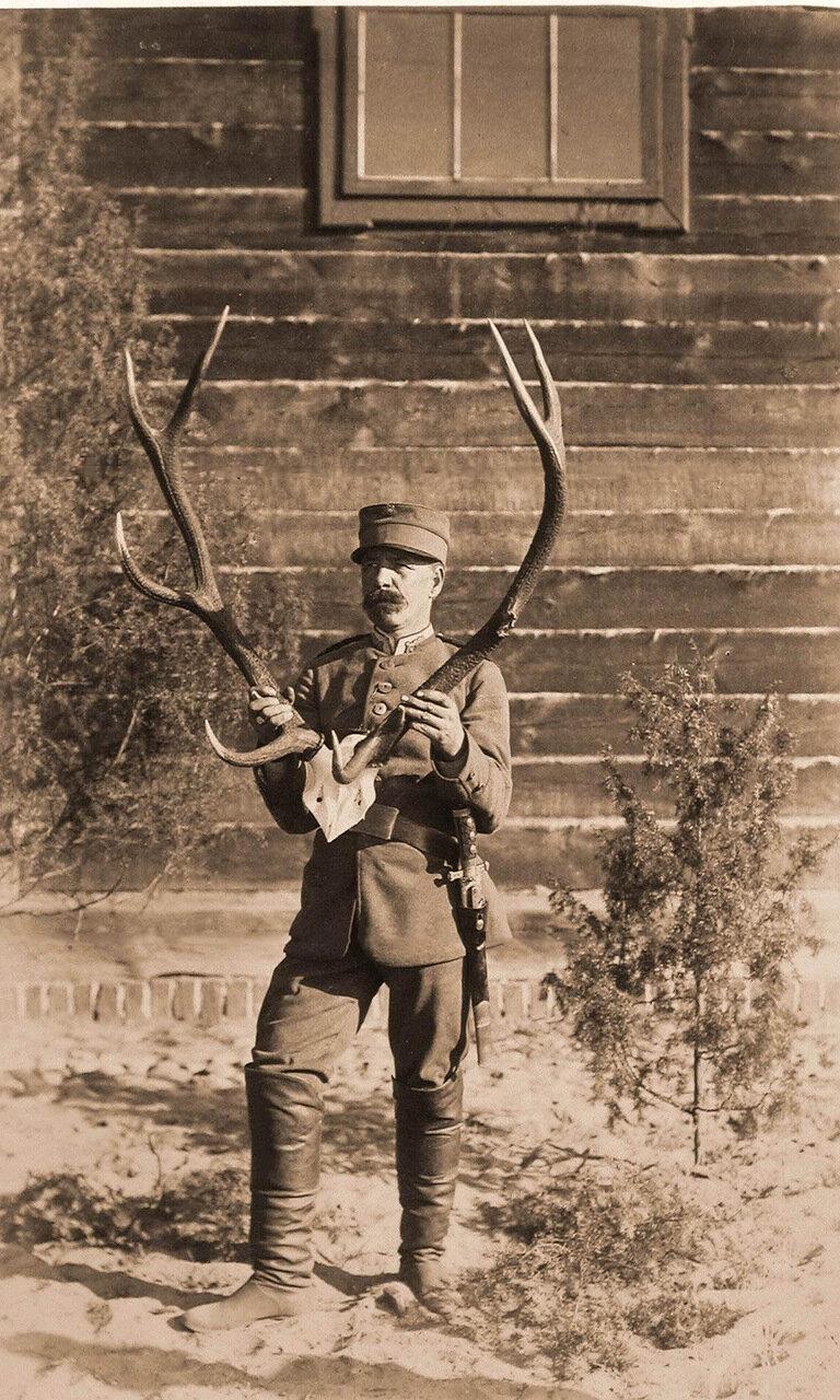 19. Один из участников царской охоты демонстрирует рога убитого оленя