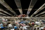 Мужчина спит под мостом среди мусора в городе Паранак, Филиппины, 31 мая 2016 года. Фото: Ezra Acayan / Reuters A man sleeps amidst rubbish under a bridge in Paranaque city, Metro Manila
