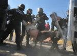 Полицейские задерживают одну из участниц акции протеста против повышения цен на топливо. Монклова, Мексика, 6 января 2017 года. Фото:    MEXICO-GASOLINE/