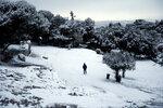 Мужчина идет по вершине холма Пникс после снегопада в Афинах, Греция, 10 января 2017 года. Фото: Alkis Konstantinidis / Reuters    GREECE-WEATHER/