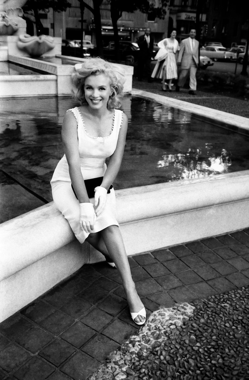 NEW YORK - 1957: Marilyn Monroe sits in front of the fountain at the Plaza Hotel in 1957 in New York