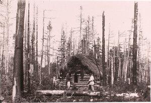 Первые поселенцы у вновь выстроенной избушки в лесу.