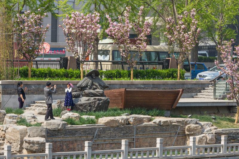 Девочка на фоне скульптурной композиции, Пекин