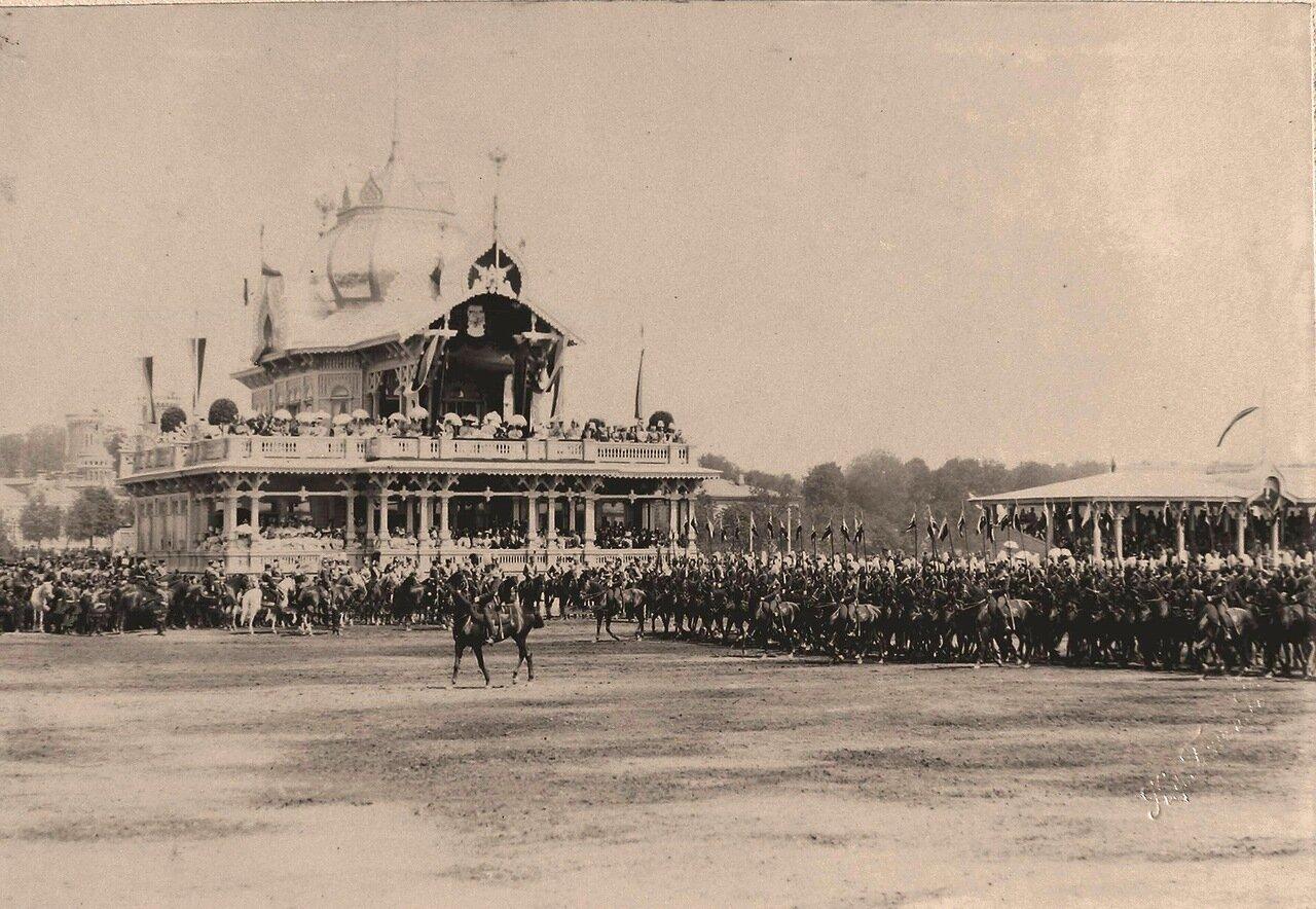 Прохождение Уланского полка церемониальным маршем во время парада на Ходынском поле; на втором плане в центре - императорский павильон, справа - гостевые трибуны для лиц дипломатического корпуса