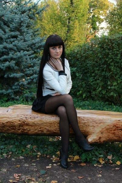 Длинноволосая брюнетка  в черной юбке и колготках