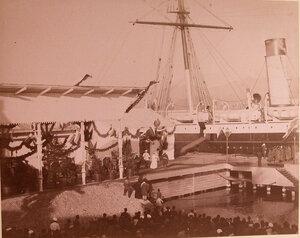 Император Александр III и императрица Мария Федоровна (в центре) направляются к яхте, стоящей у пристани.