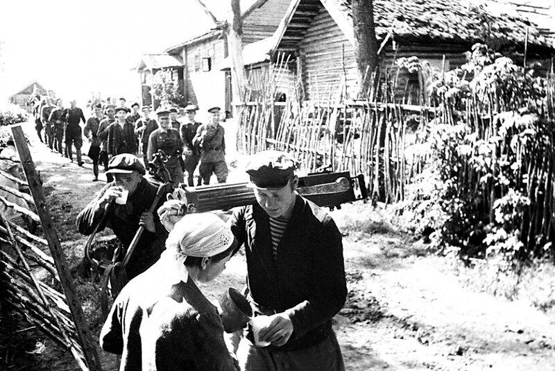 10-Деревенские жители угощают партизан молоком. 1942г.jpg