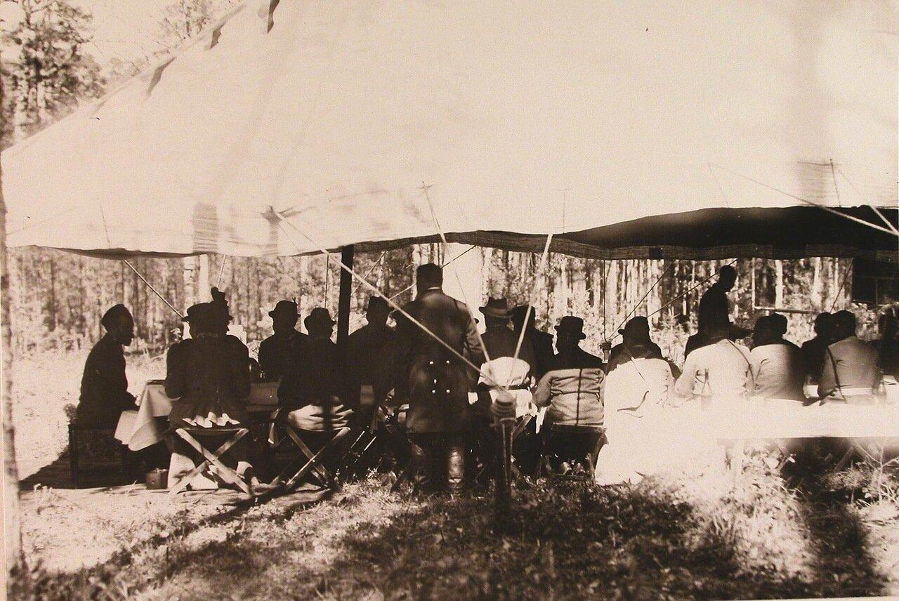 15. Группа участников царской охоты под специально установленным шатром за звтраком; крайний слева - император Николай II, рядом с ним - императрица Александра Федоровна